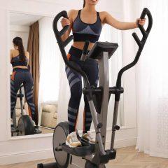 Woman using modern elliptical machine at home